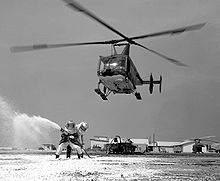 Aircraft Picture - A USAF Huskie aids a practice firefighting operation at Cam Ranh Bay AB, Vietnam in 1968. Note the aircraft's jungle camoflauge paint scheme.