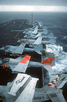 Airplane Picture - S-3A Viking, A-6E Intruder, and an EA-6B Prowler aircraft are parked on the flight deck of the aircraft carrier USS John F. Kennedy (CV-67) during a storm.