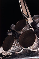 Airplane Picture - The three nozzles of the Main Engine cluster with the two Orbital Maneuvering System (OMS) pods, and the vertical stabilizer above.