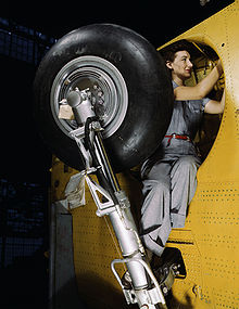 Airplane Picture - This woman worker at the Vultee-Nashville is shown making final adjustments in the wheel well of an inner wing before the installation of the landing gear. (February 1942)