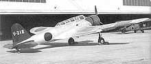 Airplane Picture - A B5N1 Kate parked in front of a hangar.