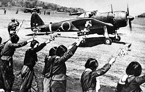 Airplane Picture - A Ki-43 III-Ko, piloted by Second Lieutenant Toshio Anazawa and carrying a 250 kg (550 lb) bomb, sets off from a Japanese airfield for the Okinawa area, on a kamikaze mission, 12 April 1945. School girls wave goodbye in the foreground.