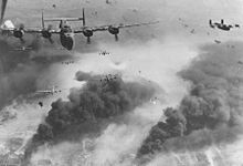 Airplane Picture - 15th Air Force B-24s fly through flak and over the destruction created by preceding waves of bombers.