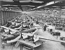Airplane Picture - B-24 Very Long Range Liberators at the Consolidated-Vultee Plant, Fort Worth, Texas in the foreground with the dark green and white paint scheme. To the rear of this front line are C-87