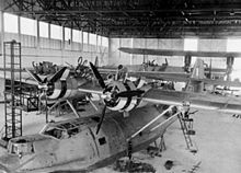 Airplane Picture - Catalina Is of 205 Sqn. RAF undergoing service in their hangar at Seletar, Singapore.