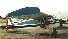 Aircraft Picture - Piper J-5A Cub Cruiser with wing endplates and banner-towing gear at North Perry airport, Florida, in March 1987