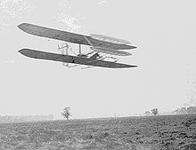 Airplane Picture - Wilbur in FlyerII Circling Huffman Prairie November 1904. The front elevator has been enlarged & the radiator moved to a rear strut since the May photo above.