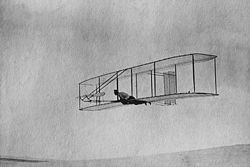 Airplane Picture - The 1902 Wright Glider (Wilbur piloting) on one of its early test flights before replacement of the fixed double rear vertical rudder with a single steerable rudder.