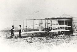 Airplane Picture - Orville(left) & Wilbur with the Wright Flyer II at Huffman Prairie May 1904. *note anemometer on strut behind Wilbur. photo possibly taken by Lorin Wright or Charlie Taylor