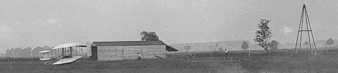 Airplane Picture - Start of the first flight of Flyer III, June 23, 1905, Orville at the controls. The catapult tower, which they began using in September 1904, is at right. It helped accelerate the aircraft to takeoff speed. The Flyer looks virtually identical to the previous two powered versions, but noticeably different from its later appearance, after the Wrights extended and enlarged the elevator and rudder. The two men are probably Wilbur (running behind the airplane) and Charles Edward Taylor (at right), the Wrights' mechanic who built their first aircraft engine.