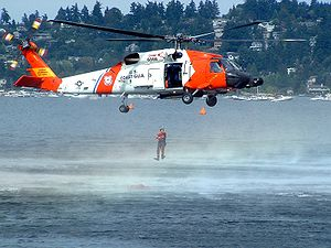 Helicopter Picture - A HH-60J Jayhawk hovering as a USCG rescue swimmer enters the water during a demonstration.