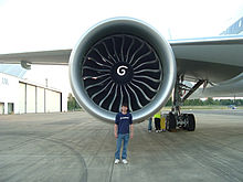 Airplane Picture - A GE90 engine mounted on a 777-300ER with a Boeing engineer to show the engine's size. Due to its size, the engine is capable of powering a Boeing 747 by itself.[74]
