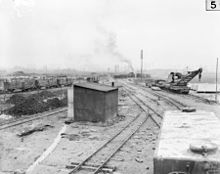 World War 1 Picture - This 1917 photo of the Poperinge yard of the Australian 2nd Light Railway Operating Company shows a water tank car in the right foreground. Behind the tank car is a partially armored, 16-wheel, hand-operated light railway crane capable of lifting 6 tons. The crane was built by Ransomes & Rapier of Ipswich, England. Cars in the left background appear to be loaded with crates of food or ammunition.