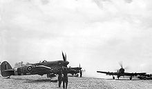 Airplane Picture - 198 Sqn. Typhoons on airfield B.7 Rucqueville-Martragny, France, in July 1944. MN526 TP-V has the larger Tempest tailplane and a four bladed propeller. A heavy dust cloud has been stirred up by the taxiing aircraft.