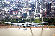 Airplane Picture - B-2 in flight over the Mississippi River (St. Louis, Missouri) with the Gateway Arch and Busch Stadium in the background