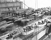 Airplane Pictures - P-38s deck-loaded on CVE, ready for shipment, cocooned against salt, at New York