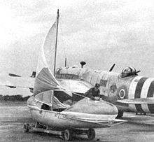 Warbird Picture - A rigged airborne lifeboat in front of a Warwick with D-Day identification stripes.
