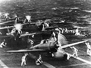 Airplane Pictures - A6M2 Zero Model 21 (front) on Shokaku. (Shokaku distinguisable from the white band on the fuselage just ahead of the tail) to attack Pearl Harbor during the morning of 7 December 1941. This is probably the launch of the second attack wave. The original photograph was captured on Attu in 1943